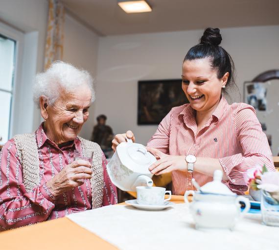 Junge Frau und Senioren trinken gemeinsam Kaffee